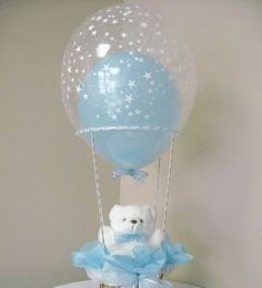 Transparent balloon filled with a single Blue balloon tied to a basket with White Teddy and Blue wrapping