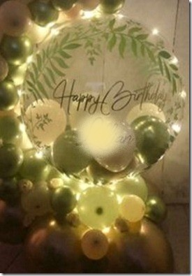 Happy birthday print on the transparent balloon with small White and green balloons stuffed inside and outside like a balloon garland decorated with foliage white flowers and led lights