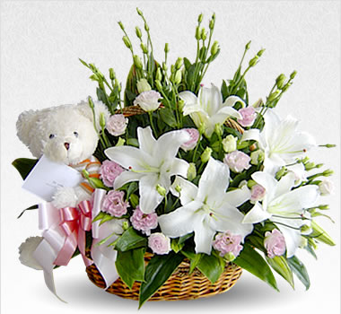 White Liliums and white teddy in a basket