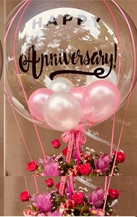Pink white small balloons air filled in a Clear Bobo Balloon with print happy anniversary attached with pink ribbons in a basket of 12 Red roses