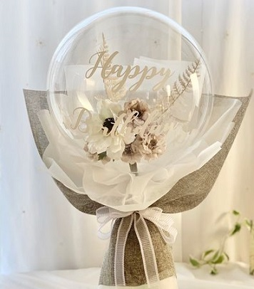 Balloon Bouquet with print happy birthday and white roses inside adorned with white and brown paper and white ribbons