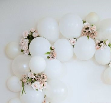15 white air filled balloon bouquet inserted at intervals with 20 pink flowers