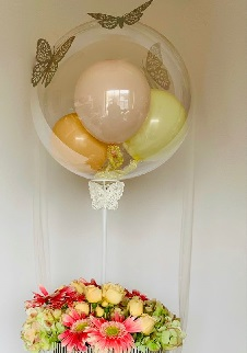 Soft color balloons inside a bubble clear balloon with butterflies and tied to a basket with pink red gerberas and peach roses