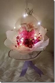 Transparent bubble balloon with 1 pink rose stuffed inside and 6 red roses outside with Led Lights wrapped in white paper and ribbons