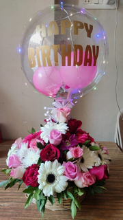 Happy Birthday printed clear balloon with pink balloons inside attached to a basket with pink red roses and white gerberas