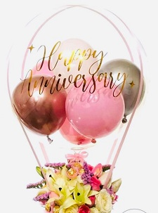 Silver Gold and Pink Balloons inside a clear balloon printed with message happy anniversary and decorated with a basket of white lilies and pink white red roses