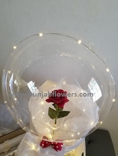 Red rose in a transparent balloon with luminous LED lights