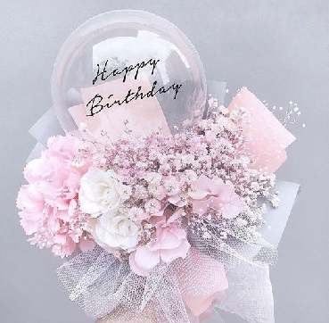 Pink and white roses on the outside of a transparent balloon with print happy birthday and decrated with pink paper and white net