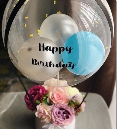 2 Silver and 1 Blue balloon inside a happy birthday print bubble balloon tied with black ribbon to a basket of 12 mix roses