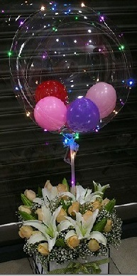 Led string lights on a clear balloon with small balloons inside and tied to a basket with 10 peach roses and 4 white lilies