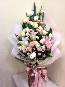 3 Light pink Lilies with 20 peach roses and 10 white roses in a bouquet wrapped in net and tied with pink ribbons