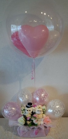 Pink Balloons in a Bubble Balloon tied to a stick with ribbons and 2 Teddy bear sitting in a basket with pink and white flowers and 4 pink white balloons basket covered with pink net